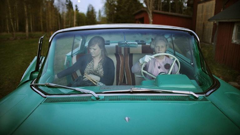 Två kvinnor sitter i en grön bil.