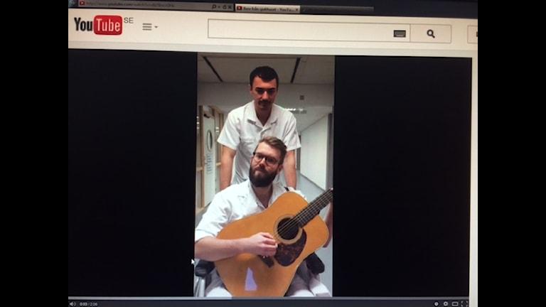 Per Hellström med gitarr och en kollega är senaste inlägget på You Tube om omorganisationen i landstinget. Foto: SR