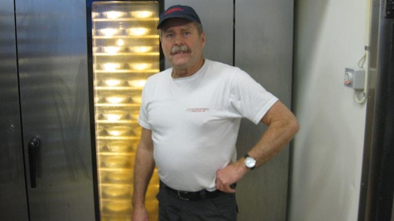 Alf Wiréhn, ostkakebagare i Vrigstad, utanför en ugn full av ostkakor. Foto: Simon Björling/Sveriges Radio.