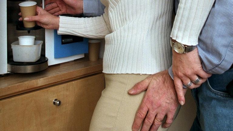 Man lägger handen på rumpan på kvinna som tar kaffe.