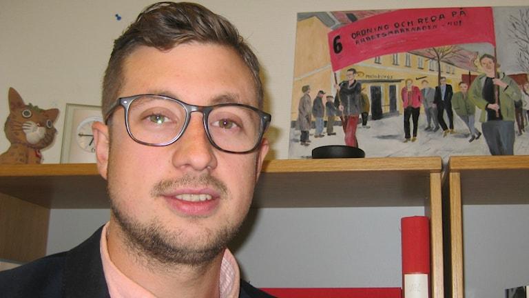 Man i glasögon med gammal målning av arbetarrörelsedemonstration i bakgrunden.
