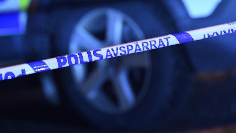 Närbild på ett polisavspärrningsband framför en polisbil.