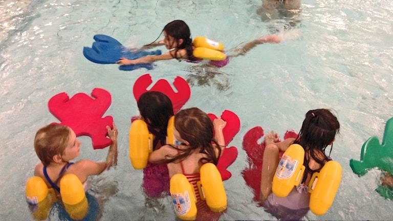Flera barn som simmar i en pool.
