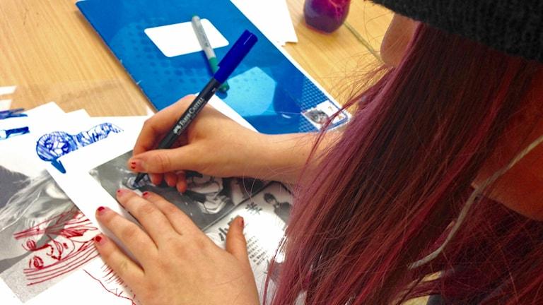 Emilia ritar självporträtt. Foto: Sanna Hermansson/Sveriges Radio