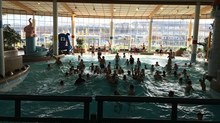 Badgäster simmar i vågorna på Rosenlundsbadet.