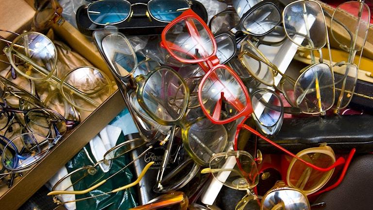 Massor av begagnade glasögon ligger i en hög. Det är allt från färgglada till gråa glasögon.