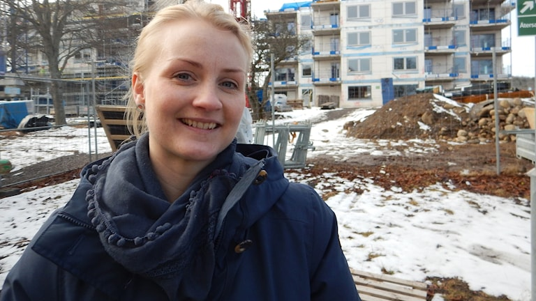 Cecilia Lind som är personalansvarig på Skanska ler in i kameran på fotot där hon står framför ett hus som byggs.