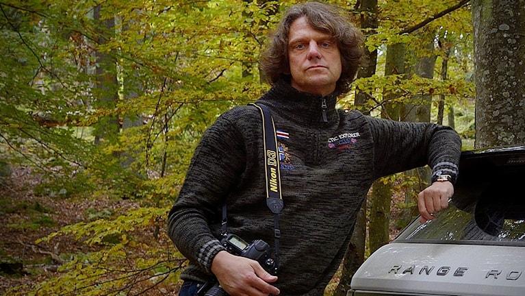 Fotografen Mats Andersson står lutad mot en bil med sin kamera hängandes över axeln.