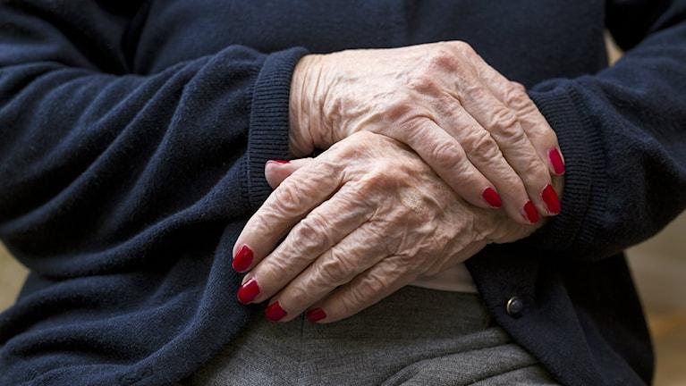 En äldre kvinna sitter med händerna i kors över magen.