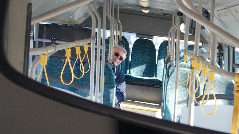 Bo Liljekvist som är busschaufför sitter på en av de bussäten som skyms av tv-skärmen.
