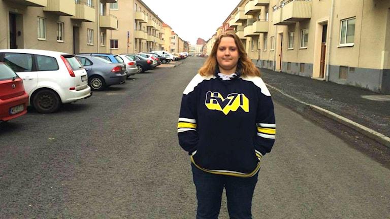 Linda Andersson från Hv71:s supporterförening står med hv-tröja på en väg.