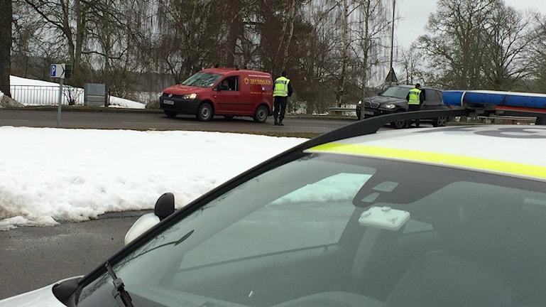 Två poliser kontrollerar två olika bilar, en röd skåpbil och en svart personbil.