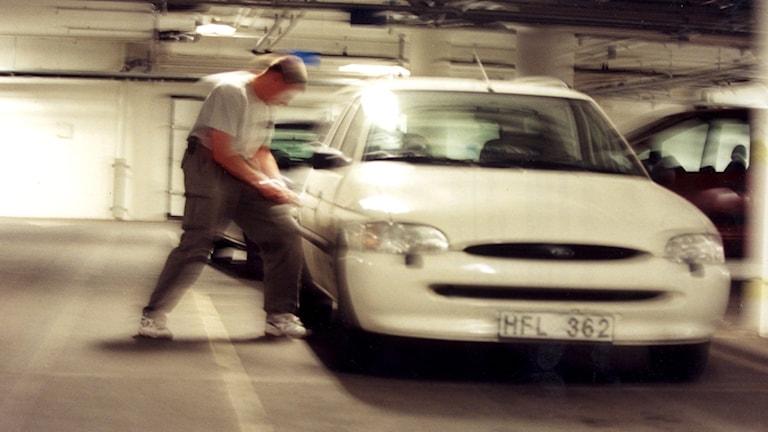 Man gör inbrott i bil i parkeringshus. Foto: Pawel Flato/TT.