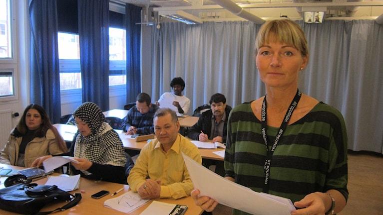 Anneli Hedström som är lärare på SFI i Vetlanda står framför en klass med sex personer från olika bakgrund som sitter i skolbänkar.