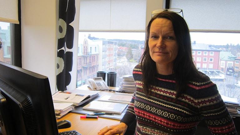 Helene Jonsson som är grundskolechef i Vetlanda kommun står framför sin dator med glasögonen uppe på hjässan.