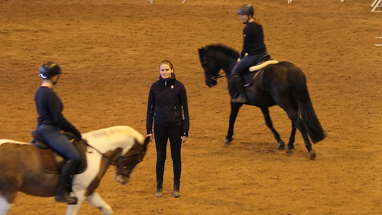 Maria Stigsson står i ett ridhus medan två ryttare på var sin häst rider runt henne.