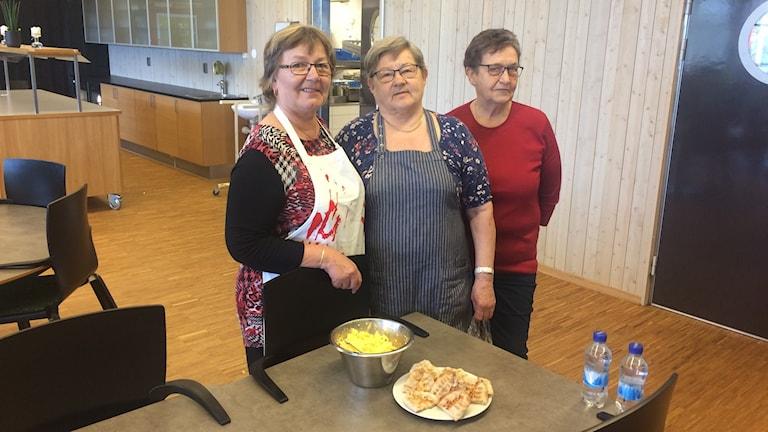 Pirkko Idström Hakala, Kerttu Rantonen och Sinikka Lepistö serverar karelska piroger i Glashuset i Gislaved i dag. Foto: Tommy Alexandersson/Sveriges Radio.