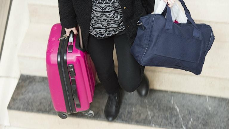 En person står med en rosa resväska i högra handen och en blå i vänstra.