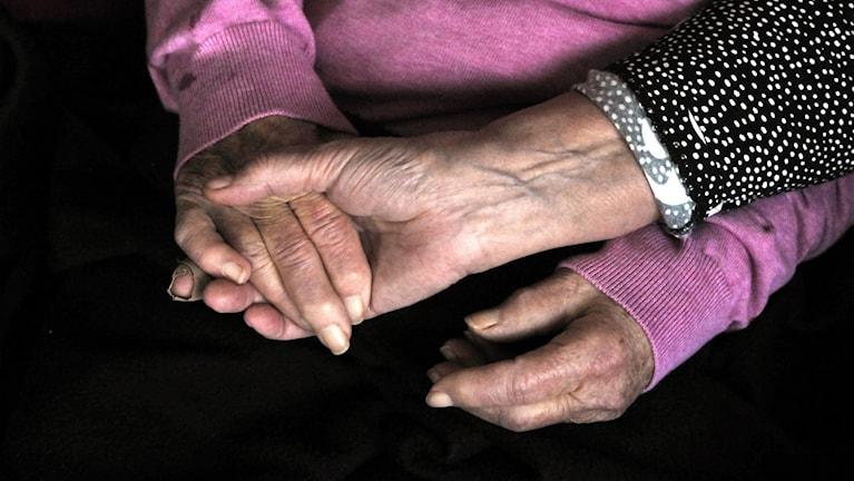 En kvinna håller en gammalkvinna i handen, det är bara händerna som syns på bilden.
