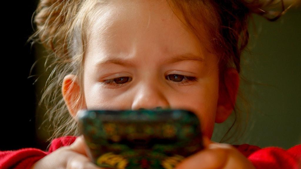 Litet barn sitter med en mobil.