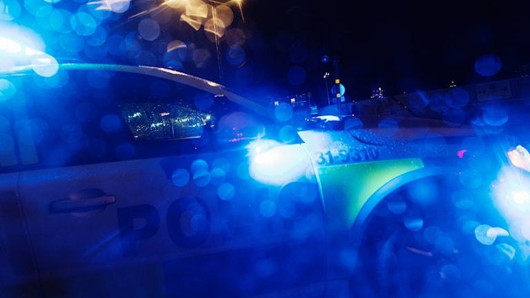 En polis med blåljus i mörker.