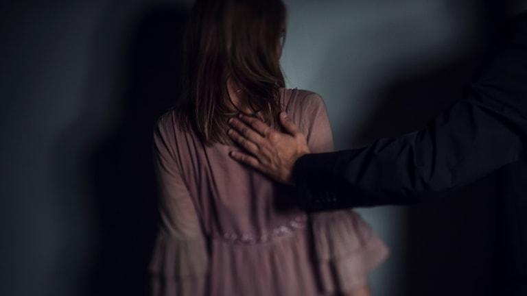 En kvinna står mot en vägg. En man håller sin hand på hennes rygg.