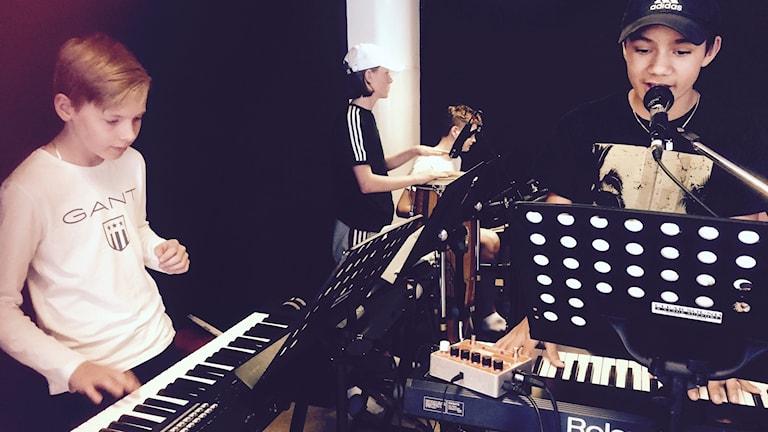 Pelle, Hugo och Linus står vid instrument.