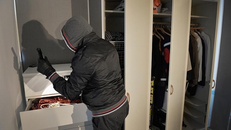 En inbrottstjuv går igenom smycken i en byrålåda.