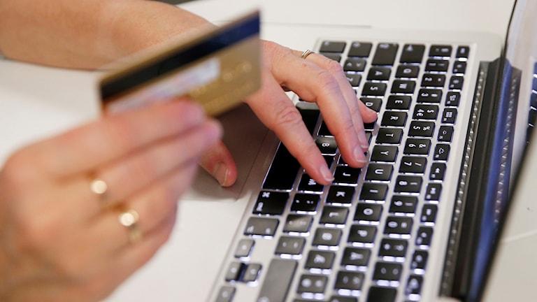 Kontokort hålls i en hand medan andra handen skriver på dator.