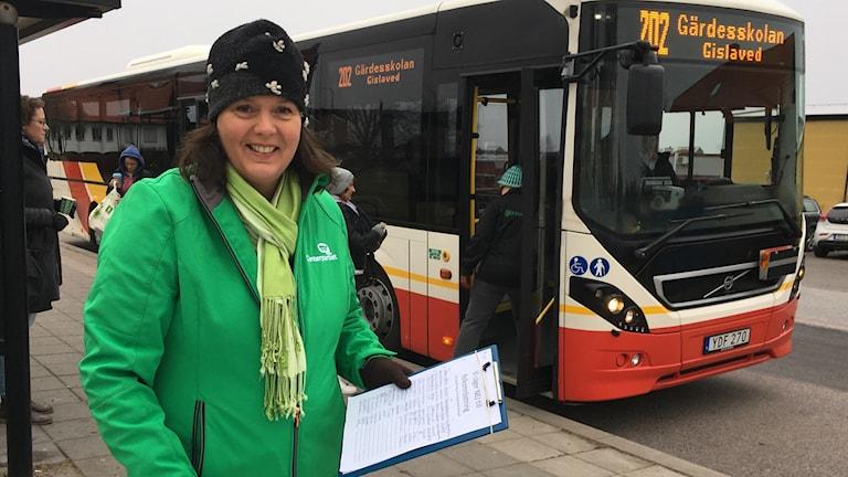 Carina Johansson (C) står med namlista vid en busshållplats i Anderstorp.