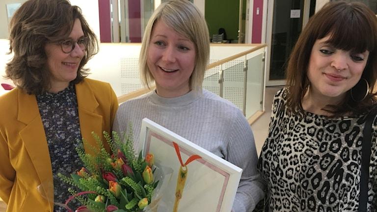 Sofie Lycksell och Patricia Svensson från Publicistklubbens östra krets med Rebecka Montelius med blommor och tavla emellan sig. Foto: Karin Selldén/Sveriges Radio.
