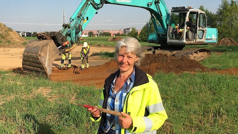 Arkeolog står vid utgrävnigsplats med hacka i handen och grävskopa i bakgrunden
