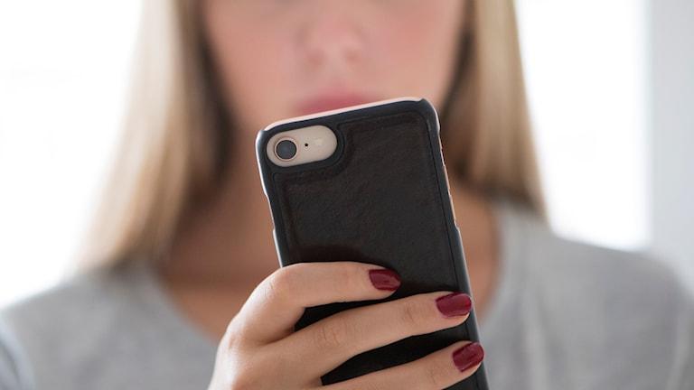 Arkivbild på tjej som håller i en mobil.