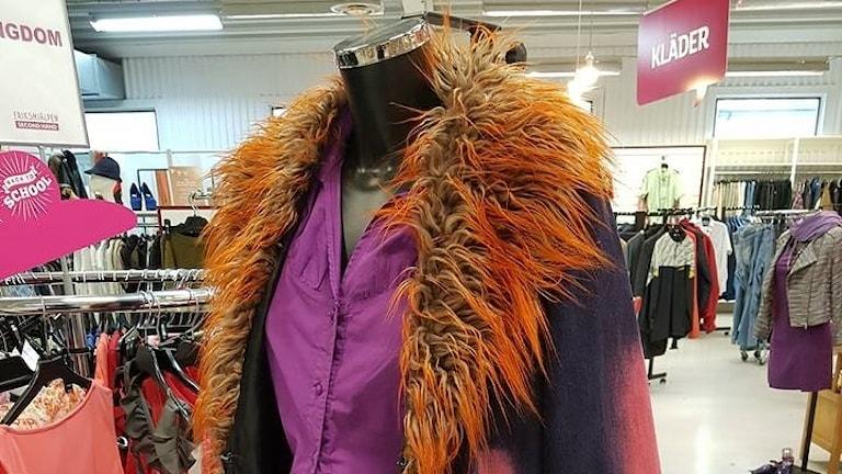En lila kappa med orange päls.