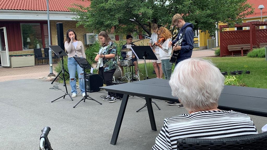 Band med unga spelar instrument och sjunger. Äldre person sitter i förgrunden.