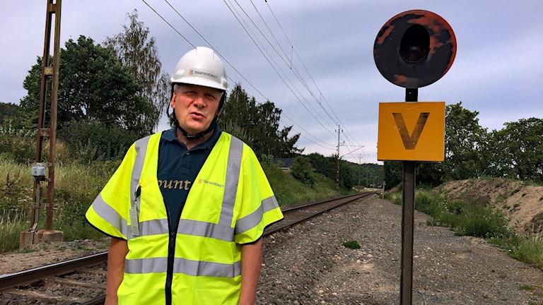 Anders Axelsson, projektledare på Trafikverket, står vid sidan av ett järnvägsspår.