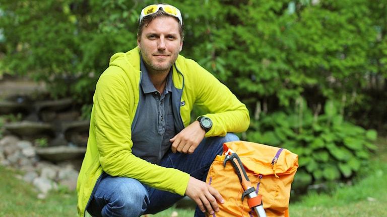 Martin Hjälle sittandes i trädgård med klätterryggsäck.
