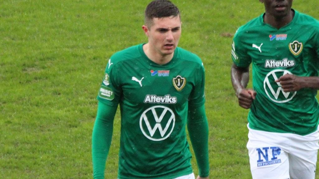 Två fotbollsspelare i grönt som går på en fotbollsplan.