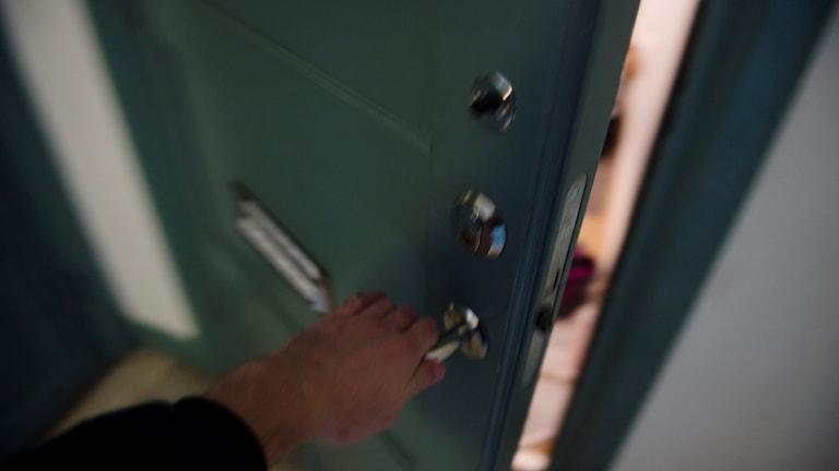 En hand öppnar en dörr till en lägenhet.