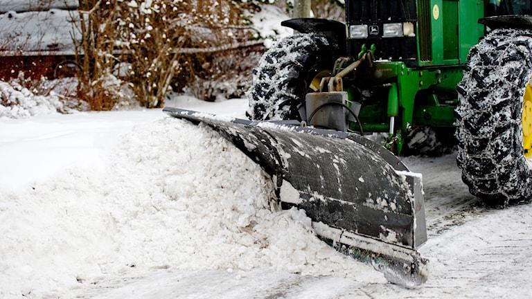 Traktor röjer snö.
