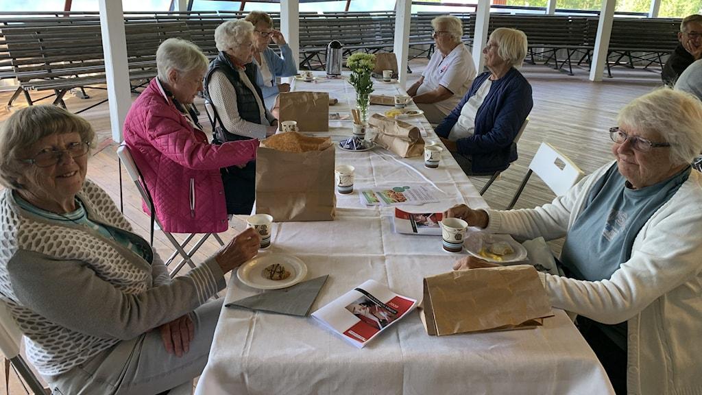 Bild på några äldre damer som sitter och fikar tillsammans runt ett bord.