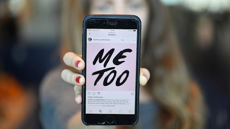 """En tjej håller fram en mobiltelefon med texten """"me too"""" på skärmen."""