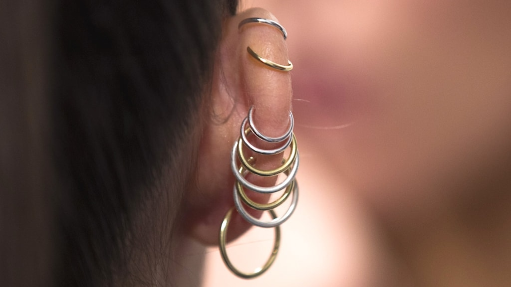 En kvinnas öra med många ringar i taget bakifrån.