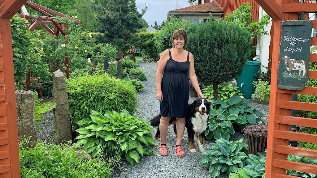 Susanne Smedberg står tillsammans med sin hund i sin grönskande trädgård.