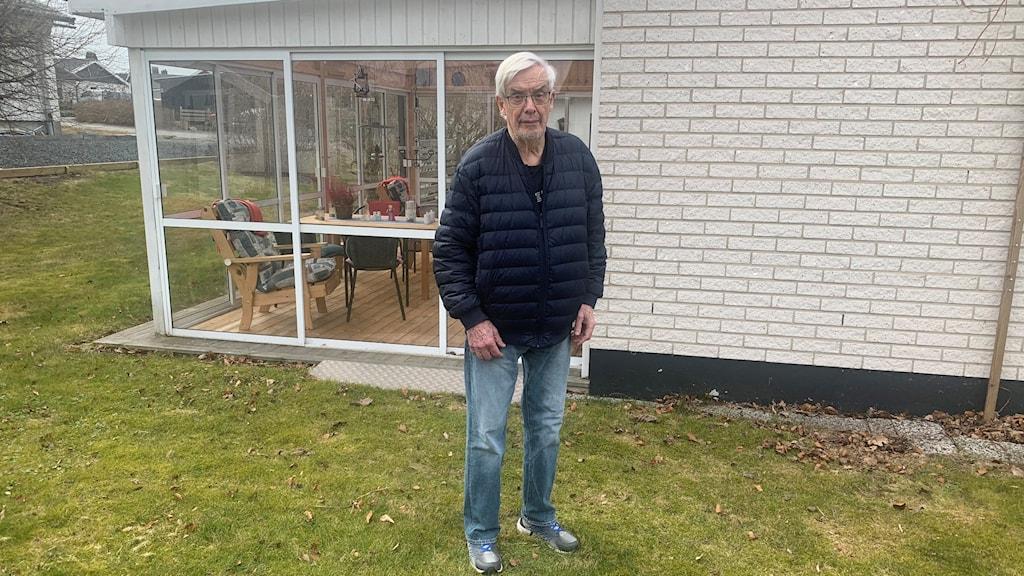 En man står på sin gräsmatta framför sitt hus.