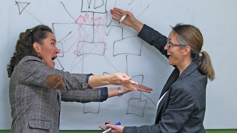 Annika Engström och Cecilia Bjursell vid ett organisationsschema.