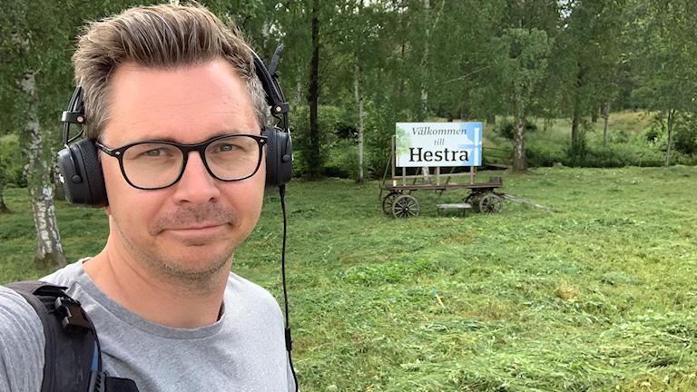 """Håkan Eng framför en skylt med texten """"Välkommen till Hestra."""""""