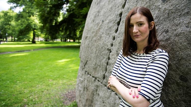 Birgitta Ohlsson lutar sig mot en stor sten och har armarna i kors.