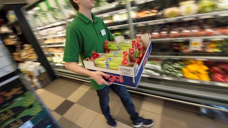 En kille som bär på en fruktlåda i en butik.