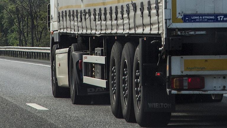 En lastbil kör på en väg.